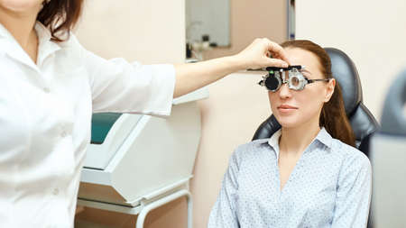Eye ophthalmologist exam. Eyesight recovery. Astigmatism check concept. Ophthalmology diagmostic device. Beauty girl portrait in clinic. Standard-Bild