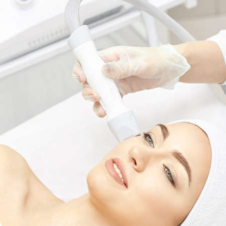 Vacuum face cosmetology equipment. Facial salon cleaning. Youn girl professional skin care. Beauty woman and health device. Zdjęcie Seryjne - 131842297