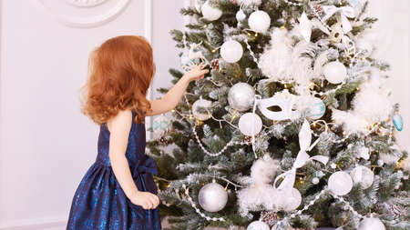 Little girl decorate tree. Christmas interior. Blue dress.
