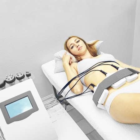 Laser lipo equipment. Cosmetic fat reduce treatment. Woman in medicine salon. Anti cellulite procedure. Foto de archivo - 139584259
