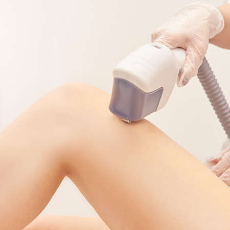 Laser elos medical device. Remove unwanted hair and asteriks. Cosmetology spa procedure at salon. Doctor laser leg depilation. Perfect treatment. Zdjęcie Seryjne