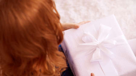 Little girl hold gift box. Red hair child smiling. Zdjęcie Seryjne