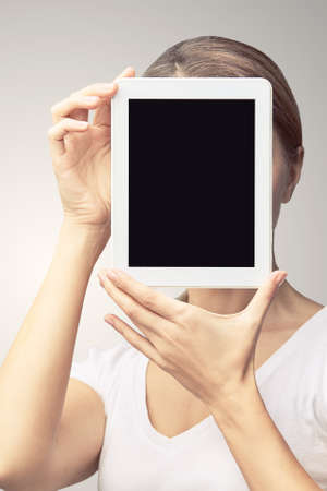 Girl holding computer pad. Mock up at tablet black screen. Face near laptop. Woman showing pc. Zdjęcie Seryjne