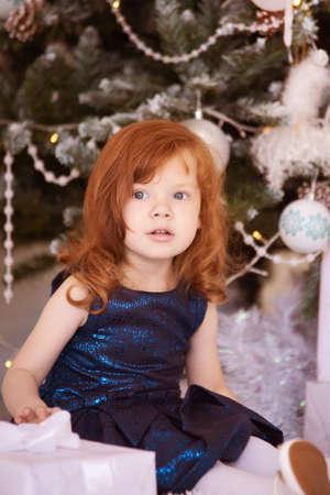 Little girl. Christmas interior. Red hair. Vertical. Stock Photo