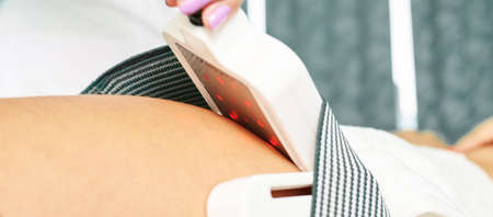 Laser lipo equipment. Cosmetic fat reduce treatment. Woman in medicine salon. Anti cellulite procedure.