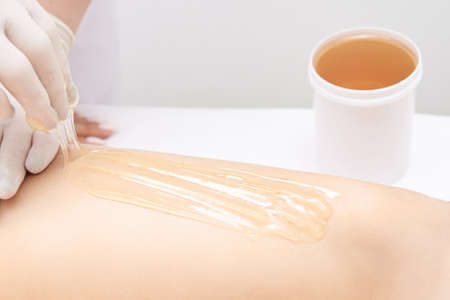 Hair removal at spa luxury studio. Woman legs wax with shugaring. Hot sugar. Product waxing bowl. Salon jar.
