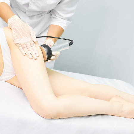 Cavitation rf body treatment. Female ultra sound lipo machine. Spa contouring. Doctor hands.