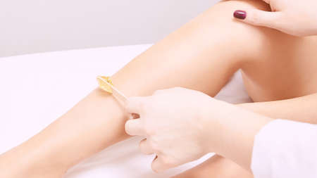 Hair removal at spa luxury studio. Woman legs wax with shugaring. Hot sugar. Zdjęcie Seryjne