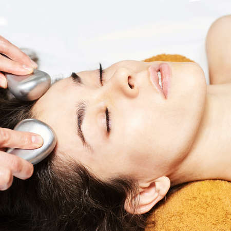 facial ice stick massage. Hot face masseur. Girl at salon with doctor hands. Stock Photo