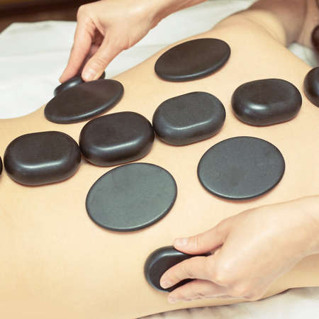 body stone massage. Hot rock masseur. Girl at salon with doctor hands. Relax spa resort.
