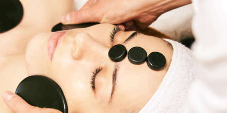 facial stone massage. Hot face masseur. Girl at salon with doctor hands. Stock Photo