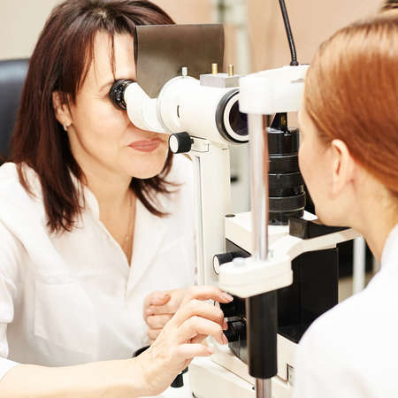ophthalmologist doctor in exam optician laboratory with female patient. Eye care medical diagnostic. Eyelid treatment
