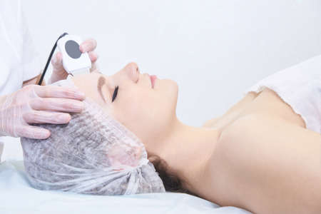 Ultrasonic cleaning of the face. Modern equipment. Cosmetic women procedure. Young girl at cosmetology salon. Doctor hands. Acne treatment device. Stock Photo
