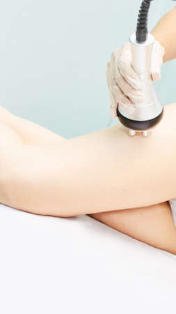 Perfect body radio treatment. Woman at spa procedure. Doctor hand and girl body. RF cosmetology lifting. Legs.