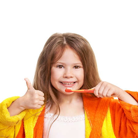 Young girl do morning dental care. Female person show thumb up. Child wash teeth. Kid clean mouth with toothbrushand bathrobe. Routine home bathroom procedure. Infant oral health cleaning. Isolated