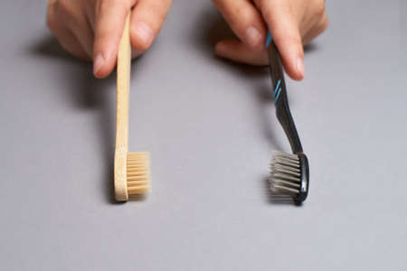 Two hands holding different types of toothbrushes. Plactic and eco bamboo brush. Black and light color or grey background Zdjęcie Seryjne - 142526221