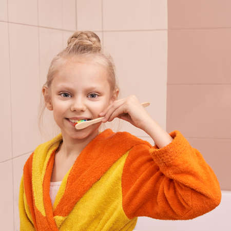 Young girl do morning dental care. Child wash teeth. Kid clean mouth with toothbrush and bathrobe. Routine home bathroom procedure. Infant oral health cleaning Zdjęcie Seryjne - 142526255