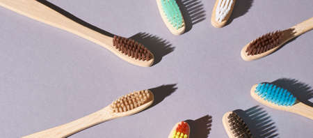 Many eco toothbrash at table. Different color bamboo tooth brush for morning hygiene routine. Diagonal photo up view. Flat lay hard shadow. Circle shape