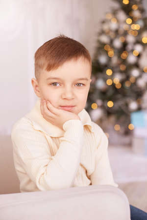 Christmas happy boy. Luxury attractive child. Xmas miracle. Green tree, lights, bokeh, new year interior. Hand near face. Look at camera. Vetrical portrait