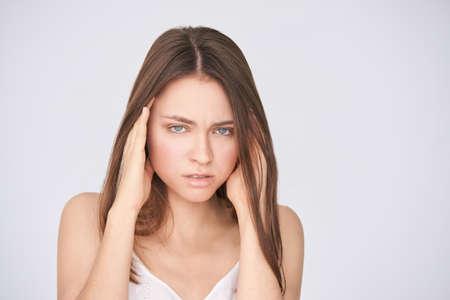 Young pretty girl with migraine. Headache woman pain. Stress sick model portrait. Negative emotion portrait. Sad people.