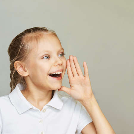 Little woman smile portrait. Side yelling with hand near head. Female kid studio portrait. Happy girl say sale discount surprise. Fun child. Grey background with copyspace.