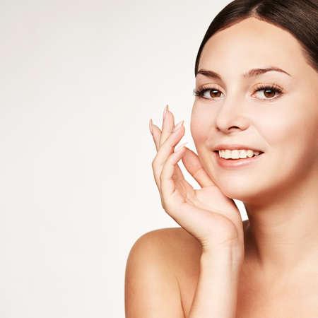 Portrait de jeune fille de beauté. Visage de femme de cosmétologie de studio avec des mains. Soin cosmétique du visage. Soins de la peau à la maison. Banque d'images