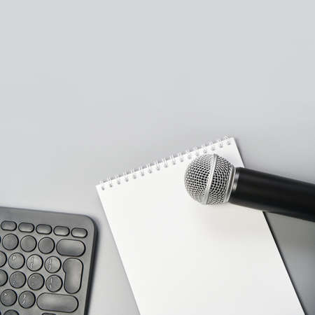 Podcast concept. White notebook with blank sheet. Black microphone, notebook and keyboard. Audiobook and podcasting. Audio technology. Home school teaching.