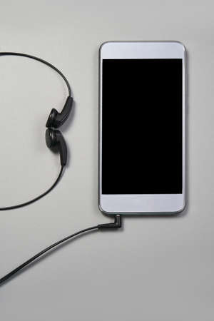Podcast concept. Phone and earphones. Grey background. Music top view. Audio technology. Hipster lifestyle. Mockup black screen. Digital culture. School homework. Lockdown accessory