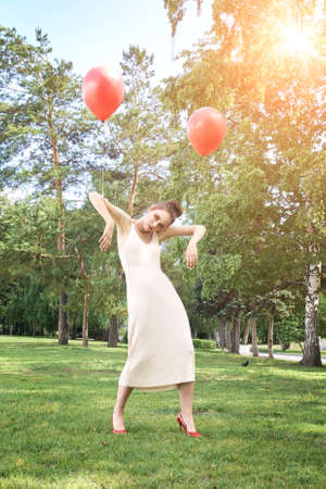 Pretty young woman with bright make up. Outdoor green portrait. Red balloons at park. Serious model face. Mascara artist style. Fashion smokey. Stand on grass. sad doll concept