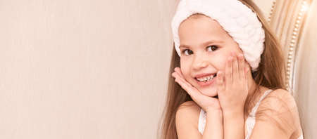 Beauty little girl posing like mom. Female home cosmetology routine. Cosmetic procedure for young skin care. Nice smile face with hands. Fresh pretty portrait