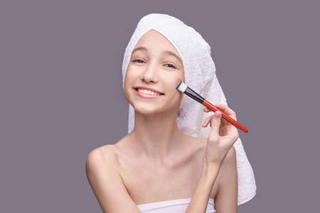 Girl with cosmetic brush. Beauty woman portrait. Peeling concept. Female person do cosmetology mask. Woman face home routine. Skin care dermatology procedure