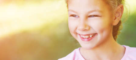Beautiful little girl smiling. Look not at the camera. Park outside the house. Advertising photo. Positive child after quarantine. End lockdown. Horizontal banner. Copyspace