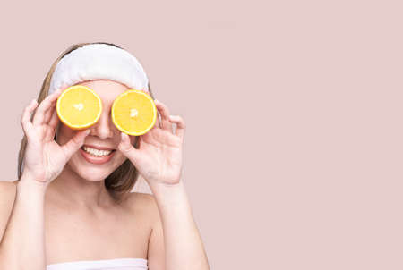 Girl hold orange slice. Citrus fruit hidding face. antioxidant home care routine. Facial energy product. Laughing portrait. Modern nature cosmetic. Ecology beauty