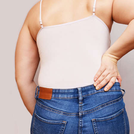 Woman lower back pain. Hold hand near body. Self chiropractic massage. jeans and top shirt. Sport muscle nerve displacement