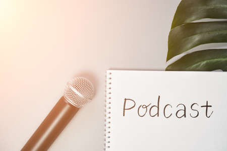 Podcast concept. White notebook with blank sheet. Black microphone and green monstera leaf. Audiobook and podcasting. Audio technology. Home school teaching. Stockfoto