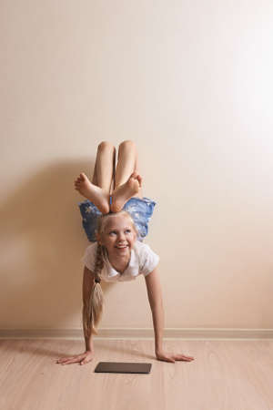 Girl playing with tablet. Not usial use equipment. Child learn at home lifestyle. Female kid holding mobile laptop. Copyspace. Electronic device. Little person reading upside down