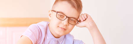 Little boy in eyeglasses thinking at home. Schoolboy study. Male child nerd. Young myopia. Student do homework. Online education. Light interior. Dreaming person. Horizontal banner with copyspace
