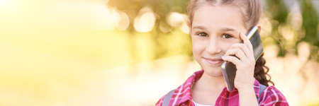 Cute little girl talking. Hold phone near face. Young woman smile. Looking at camera. Outdoor school. Green background. Smiling speach. Happy expression. Student lifestyle. Horizontal banner Foto de archivo