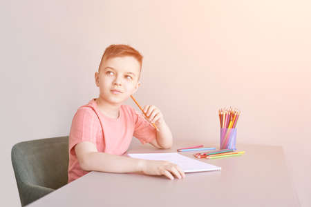 Little boy drawing. Closed Locking Exercise. Homemade routine. School lessons. Write pencil on piece of paper. Home study. Elementary preschool. Male kid student. Thinking or dreaming