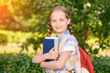 Young schoolgirl with backpack. Lifestyle going to classroom. Outdoor autumn park. Children learn smart. Street student. Happy preschool kid. Back to school. Holding books