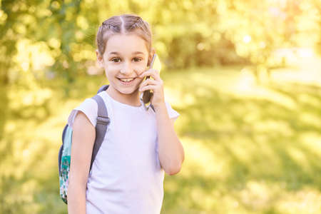 Cute little girl talking. Hold phone near face. Young woman smile. Looking at camera. Outdoor school. Green background. Smiling speach. Happy expression. Student lifestyle