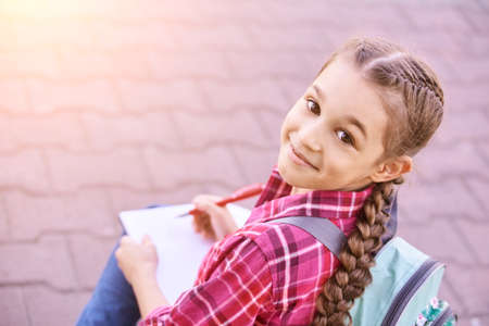 Little girl drawing. Homemade routine. School lessons. Write pen on piece of paper. Kindergarten study. Elementary preschool. Woman kid student. Thinking or dreaming. Smile child. View above. Outdoors Foto de archivo