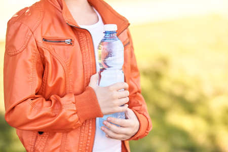 Little girl holding water bottle. Outdoor training. Thirsty. Plastic drink. Summer time. Pretty teenager lifestyle. Sunny day. Kid hand. Happy people.