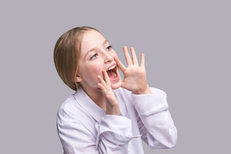 Girl shout. Little lady scream about sale. Looking side. Pretty kid with hands near head. Child portrait. Modern loud. Positive emotion. Sound on. Yelling face. Rumor concept