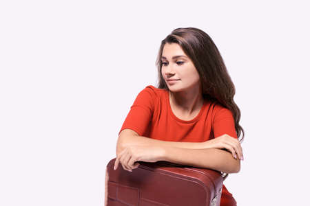 Journey. Girl with a suitcase. Pensive brunette. Red dress. Vacation concept. Staycation luggage. Woman travel alone. Single trip. White background. Copyspace