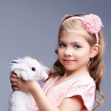 Little pretty girl holding fur rabbit baby. White cute pet at studio. Happy easter hug. Female person hand. Smile people child. Young people. Foto de archivo