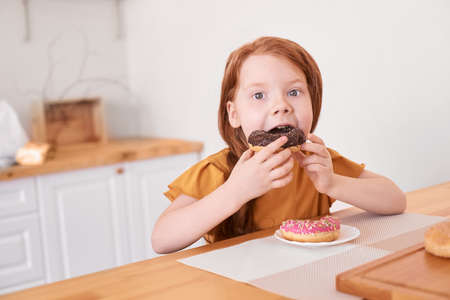 Little girl eating round doughnut. Sweet desert. Unhealthy food. Home lockdown lifestyle. Funny breakfast. Looking not in camera. Choco brown donut. Copyspace
