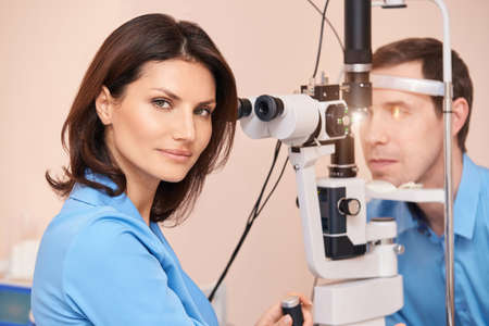 Eye doctor diagnostic. Patient at medical clinic. Cataract ophthalmology exam. Astigmatism examination. Prevention eyecare consultation. Patient control glaucoma