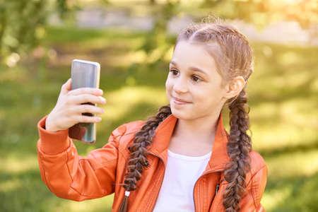 Little girl doing selfie. Happy pretty kid.