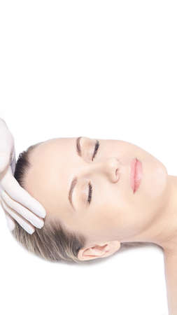 Girl lying in cosmetology spa. Face massage. Doctor hand with protective glove near head. Medical skin care. White background. Close eyes. Rejuvenation procedure. Cream cosmetics. Vertical, copyspace